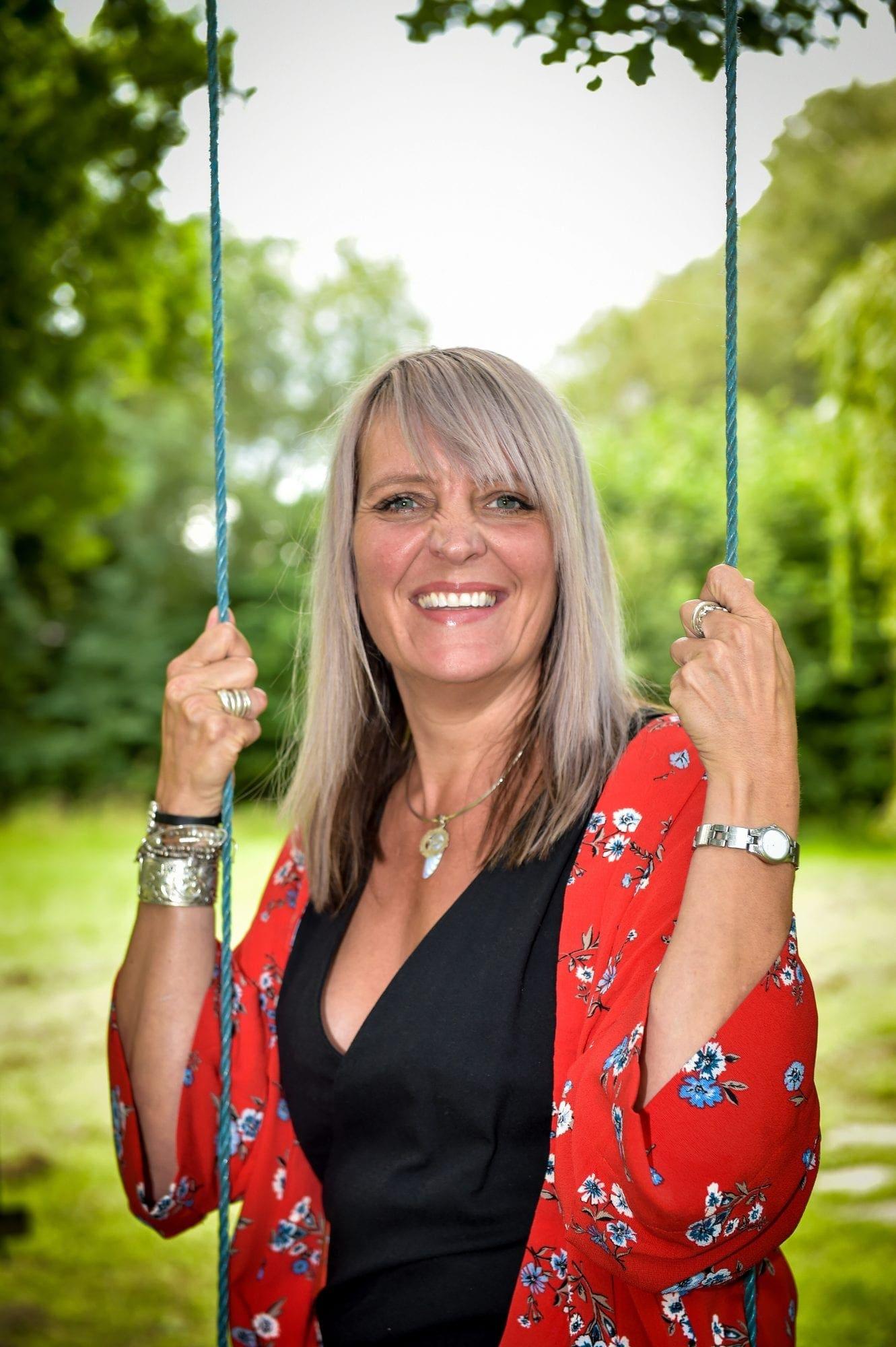 yoga teacher on swing in garden